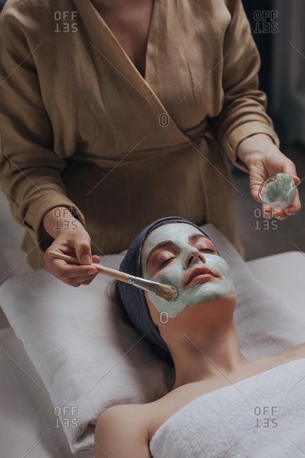 Portrait of pretty Caucasian woman enjoying beauty mast face treatment at spa salon.