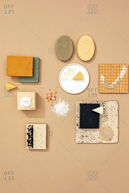 Minimalistic composition of natural soaps and cosmetic creams and spa products on pastel background.