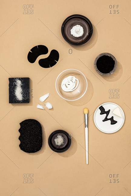 Minimalistic composition of face skin care black and white cosmetic products on pastel background.