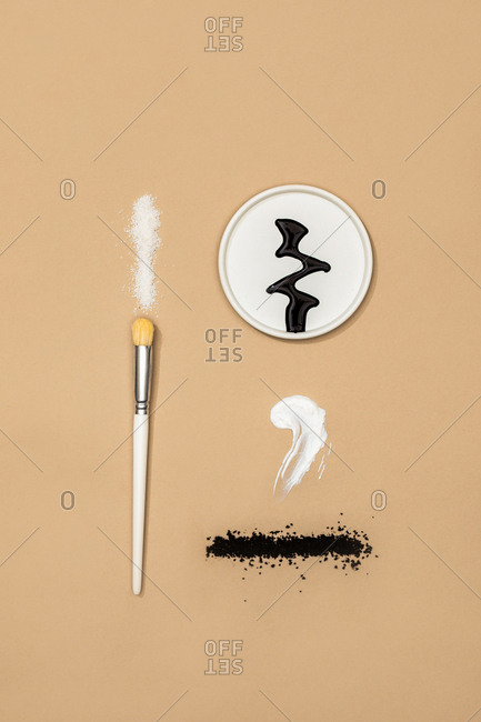 Minimalistic composition of natural cosmetic creams and scrubs and a brush on pastel background.