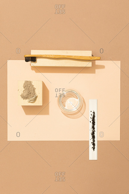 From above photo of natural cosmetic scrubs and wooden toothbrush.
