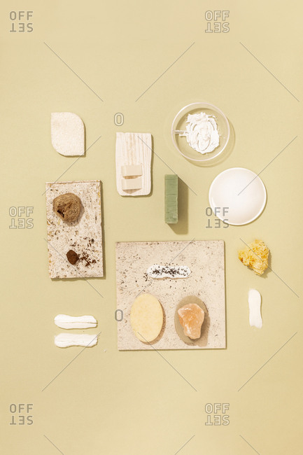 Minimalistic composition of natural soaps and cosmetic creams and scrubs on pastel background.