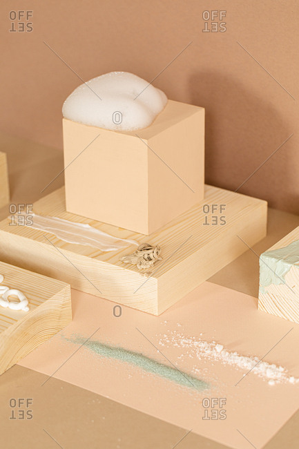 Composition of soap foam scrubs and cream on wooden objects.