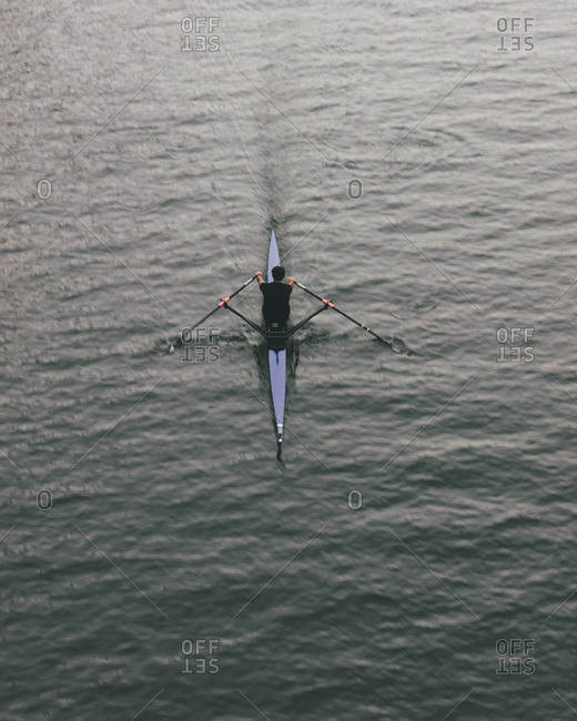 Overhead view of an oarsman in a single scull boat on calm water mid stroke, motion blur.