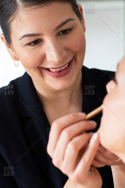 A professional make up artist at work, creating a look for a young woman.