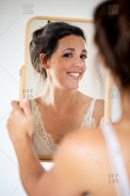 A professional make up artist at work, smiling woman holding mirror.