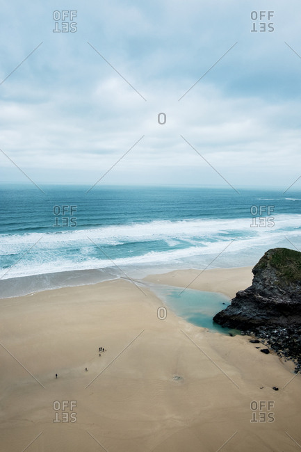 Ocean waves crashing onto a sandy beach under a cloudy sky, high angle view.