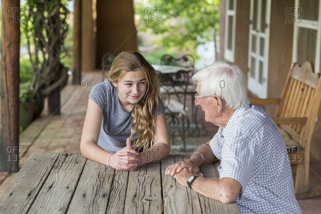 A teenage girl having a conversation with her grandfather