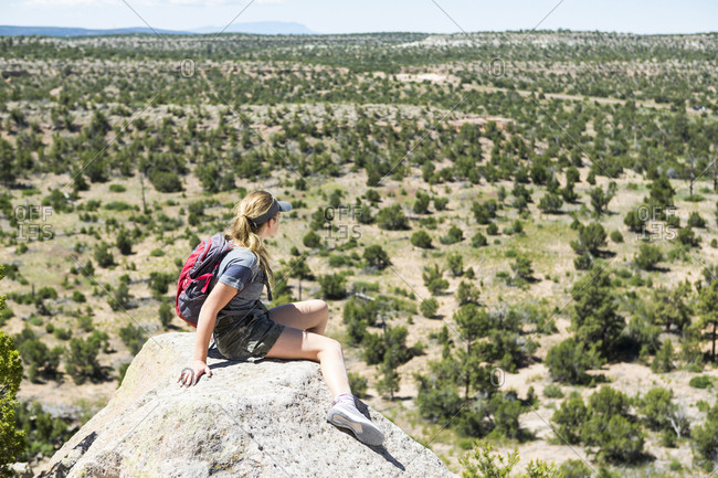 Rear view of a teenage girl hiker overlooking desert vista