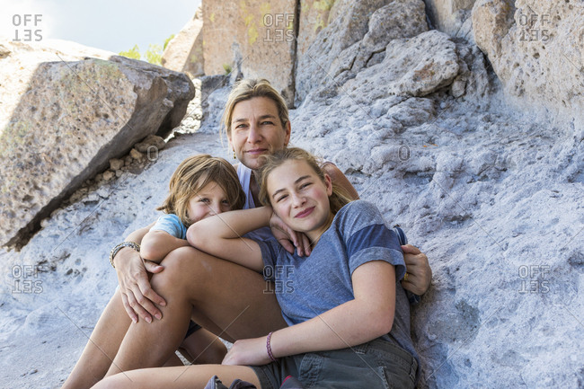 mother and her children sitting on rocks at a desert historic site in New Mexico