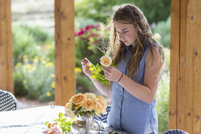 A teenage girl arranging roses from formal garden