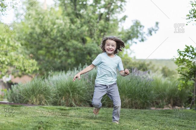5 year old boy running on green lawn