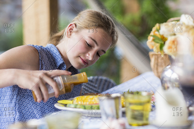 A teenage girl pouring BBQ sauce on ribs and corn