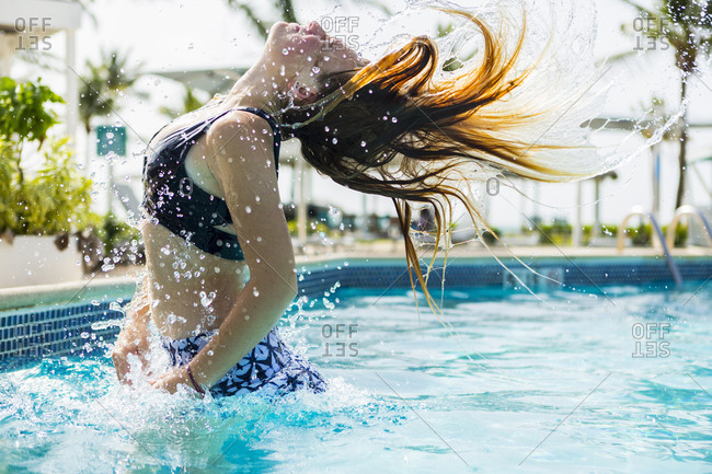 A teenage girl leaping out of the pool