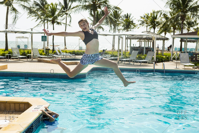 A teenage girl leaping into pool