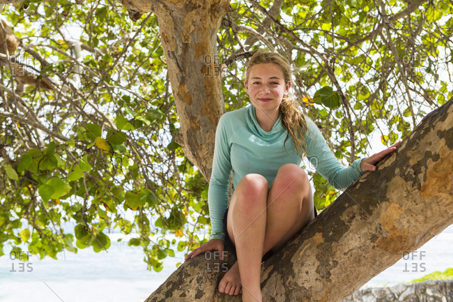 A teenage girl sitting in a tree laughing.