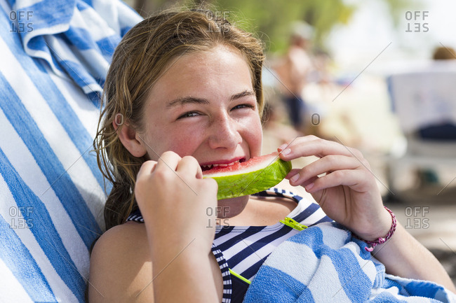 A teenage girl eating watermelon