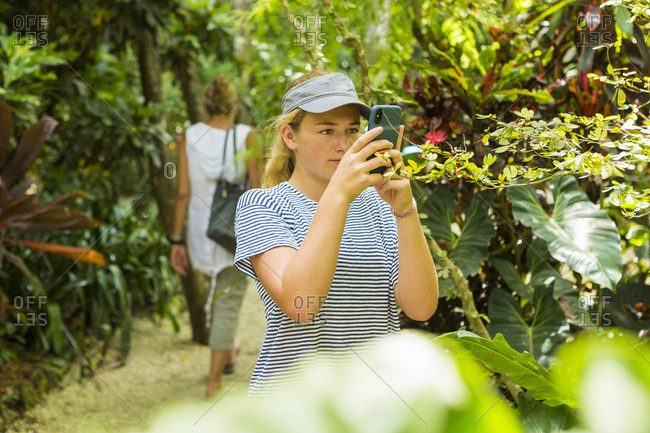 A teenage girl photographing with a smart phone on nature trail