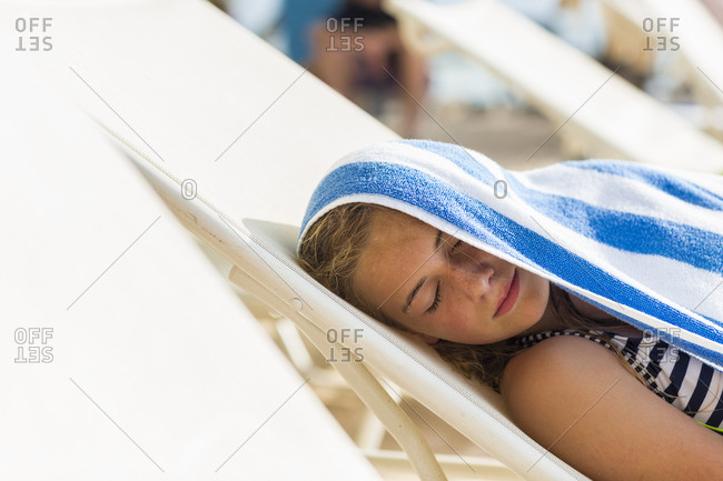 A teenage girl reclining in beach chair with towel on her head