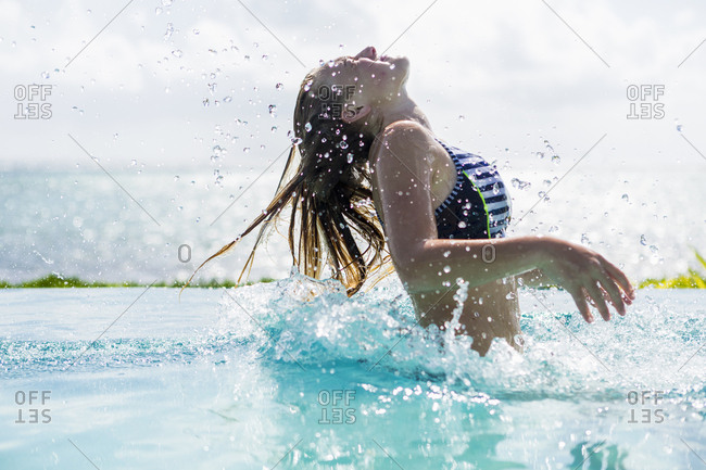 A teenage girl in infinity pool, tossing her hair back