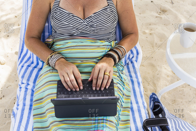 adult woman executive using laptop on the beach