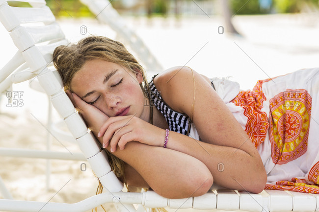 A teenage girl sleeping in beach chair