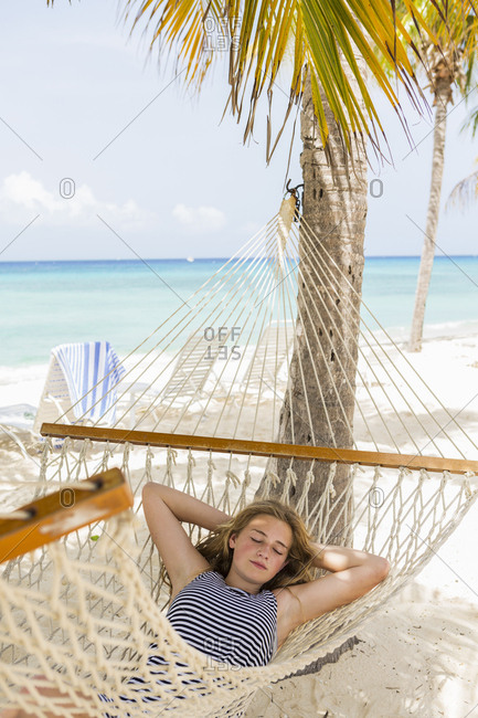 A teenage girl relaxing in a hammock on the beach