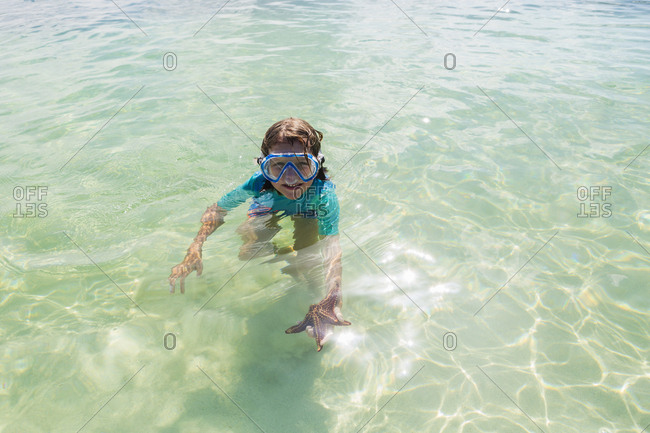 5 year old boy in the water holding a star fish