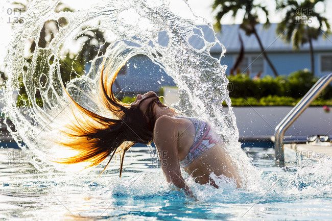 A teenage girl tossing her wet hair back, in pool