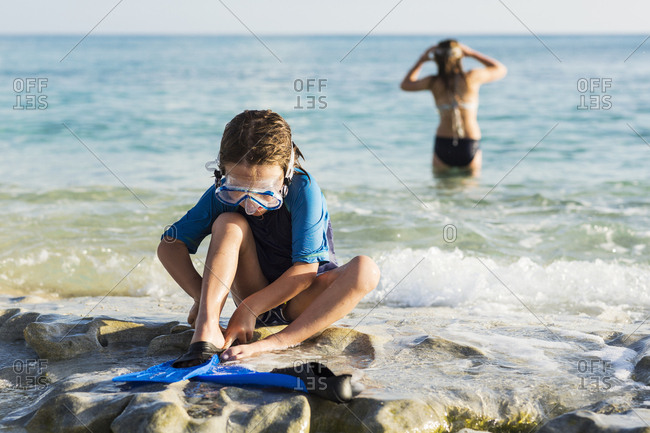 5 year old boy putting his swim fins on at the beach