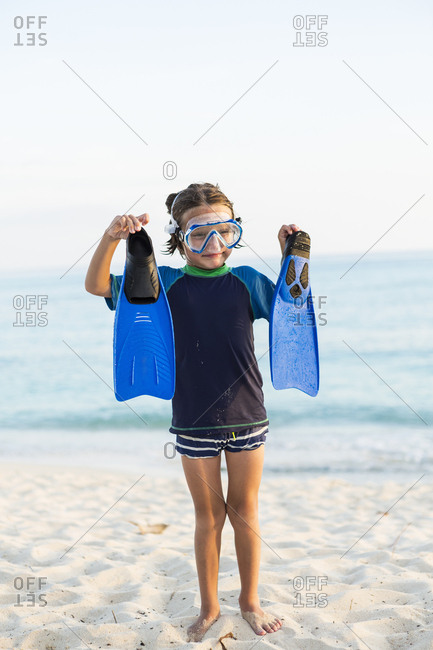 A young boy wearing a snorkel mash and holding up his blue flippers.