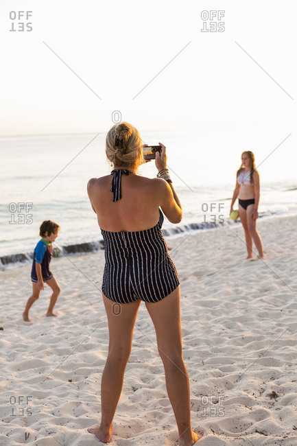 mother and her children enjoying the beach at sunset