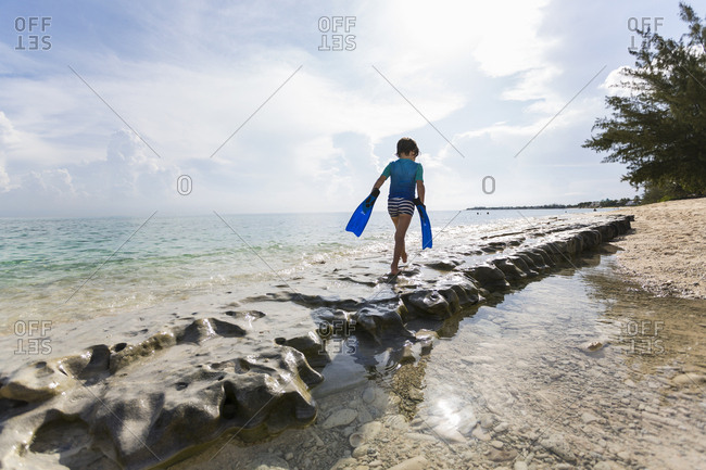 5 year old boy walking on rocks on the shore with swimming fins