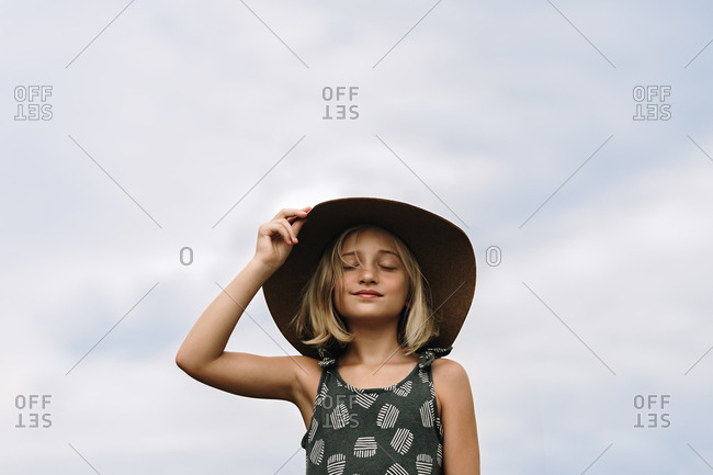 Little girl wearing large hat in front of cloudy sky