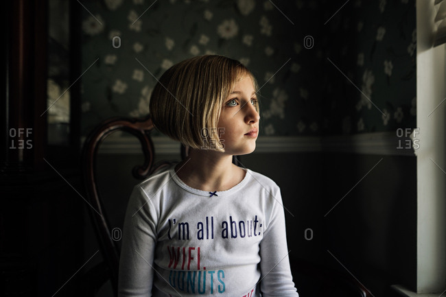 Little girl with blonde short hair sitting on chair by window