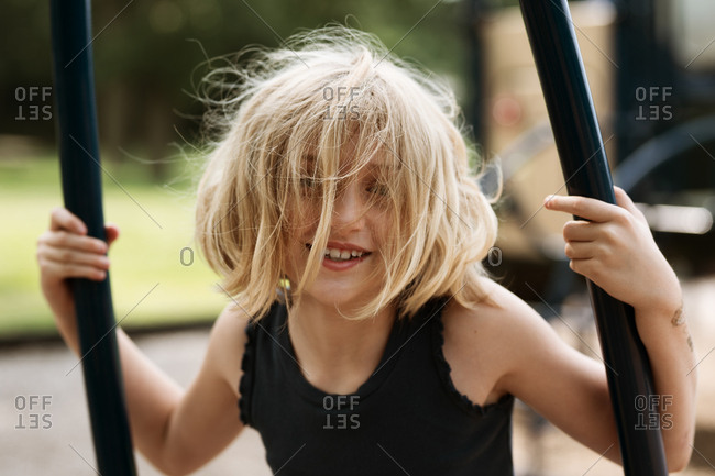 Little girl with crazy blonde hair playing on playground