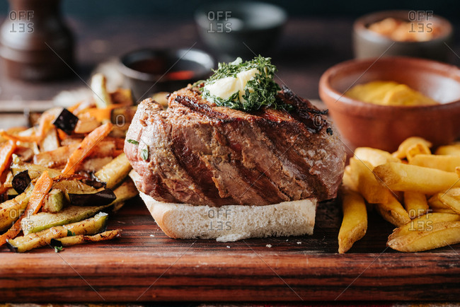 Beef steak on a wooden board with French fries