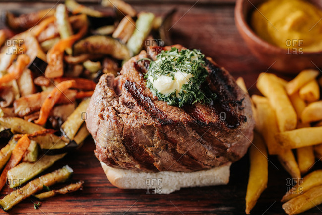 Beef steak served on a wooden board with French fries