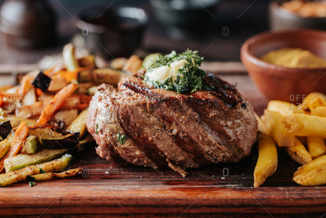 A juicy beef steak on a wooden board with French fries