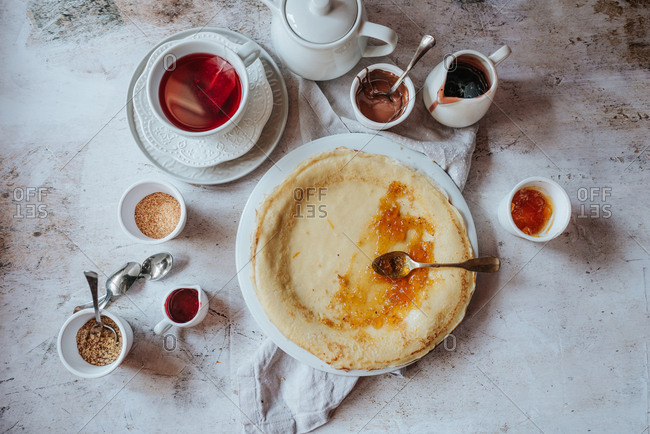 Overhead view of traditional Serbian crepes with apricot jam and tea