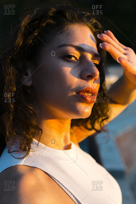 Close up of a seductive ethnic young woman covering face with hand at sunset