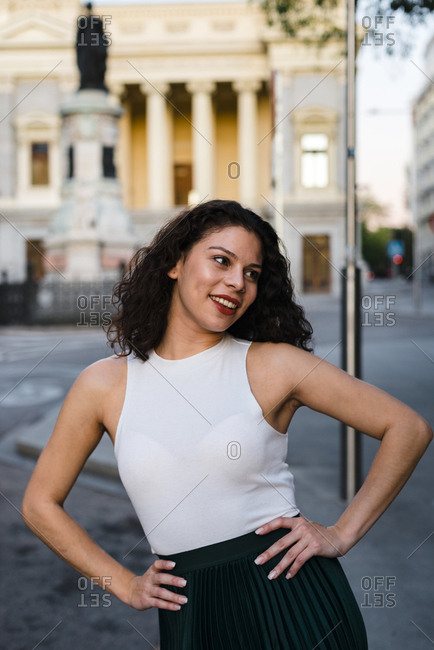 Cheerful beautiful lady in tank top and green skirt looking away with hands on waist in city street at sunset