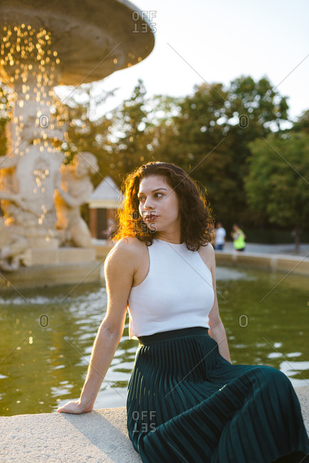Beautiful lady in tank top and green skirt looking away seated on fountain ledge at sunset