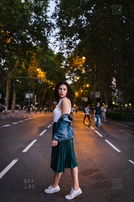 Serious millennial woman with denim jacket looking back on street between green trees and city lights