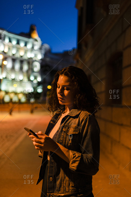 Stylish woman in denim jacket and using Smartphone on street with city lights at dusk