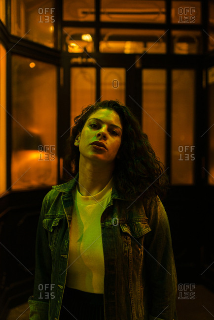 Serious woman with denim jacket looking at camera under green neon city lights