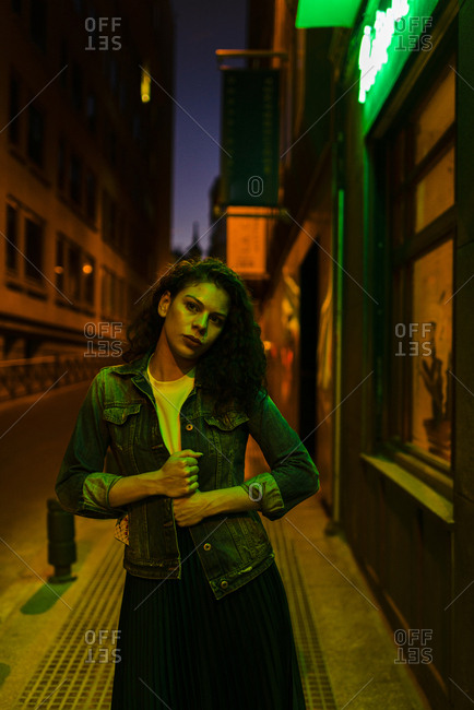 Serious millennial woman with denim jacket looking away under green neon city lights