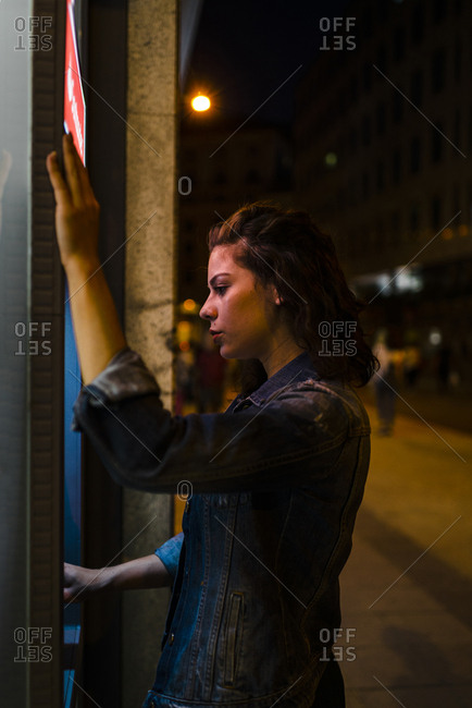 Millennial woman with denim jacket withdrawing money from ATM