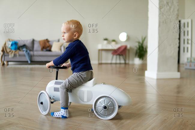 Blonde toddler boy riding on pedal car