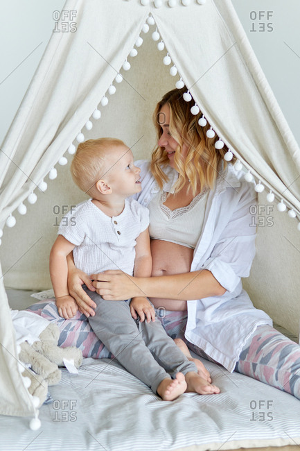 Pregnant mother and toddler son sitting inside indoor tent